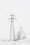 Línea de torres de la transmisión al horizonte en invierno imagen de archivo libre de regalías