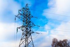 Línea de transmisión de poder torre contra el cielo azul y clowd con sn Foto de archivo libre de regalías