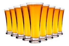 Línea de vidrios con la cerveza de cerveza dorada Foto de archivo