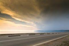 Línea del largo camino y del mar, del lago o de océano en puesta del sol Fotos de archivo libres de regalías