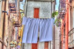 Línea del lavadero con las hojas de cama en la ciudad vieja de Bosa, Cerdeña Fotografía de archivo