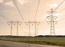 Línea eléctrica de alto voltaje en paisaje de la puesta del sol Imagen de archivo