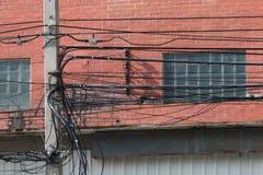 Línea eléctrica de Electrica y línea de comunicaciones en ciudad Foto de archivo libre de regalías