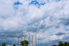 Línea eléctrica eléctrica contra la nube y el cielo azul Fotos de archivo libres de regalías