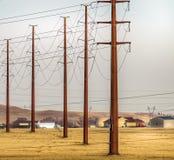 Línea eléctrica en el campo amarillo, prado del polo con el cielo tempestuoso Paisaje rural, los E.E.U.U. Imagen de archivo