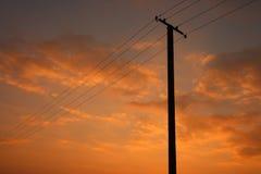 Línea eléctrica en el cielo anaranjado Imágenes de archivo libres de regalías