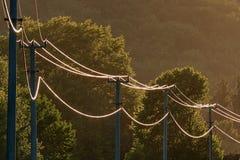 Línea eléctrica eléctrica iluminada por puesta del sol Fotografía de archivo libre de regalías