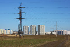 Línea eléctrica y casas contra el cielo azul Imágenes de archivo libres de regalías