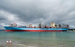 Línea enorme de Maersk del buque de carga en una bahía con los niños en primero plano Imagen de archivo libre de regalías