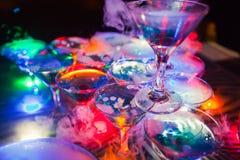 Línea hermosa de diversos cócteles coloreados del alcohol con humo en una fiesta de Navidad, un tequila, un martini, una vodka, y Imágenes de archivo libres de regalías