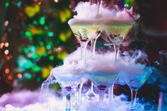 Línea hermosa de la pirámide de diversos cócteles coloreados del alcohol con la menta en la fiesta de Navidad, el tequila, martin foto de archivo libre de regalías