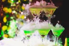 Línea hermosa de la pirámide de diversos cócteles coloreados del alcohol con la menta en la fiesta de Navidad, el tequila, martin imagen de archivo