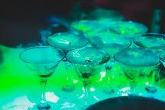 Línea hermosa de la pirámide de diversos cócteles coloreados del alcohol con la menta en la fiesta de Navidad, el tequila, martin imagen de archivo libre de regalías