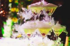 Línea hermosa de la pirámide de diversos cócteles coloreados del alcohol con la menta en la fiesta de Navidad, el tequila, martin fotos de archivo libres de regalías