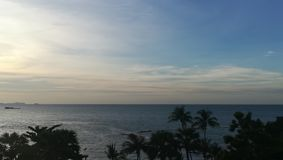 línea horizontal azul del cielo en el mar y los árboles verdes imagenes de archivo