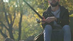 Línea para el morder grande que espera de la bobina del pescador, pescando, actividad real de los hombres almacen de metraje de vídeo