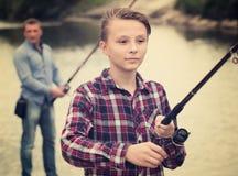 Línea positiva del bastidor del muchacho para pescar en el lago Imagenes de archivo