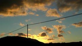 Línea telefónica contra el cielo azul y anaranjado en la puesta del sol con la mudanza de las nubes coloridas almacen de metraje de vídeo