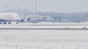 Líneas aéreas A380 de los emiratos que llevan en taxi en pista nevosa almacen de metraje de vídeo