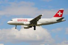 Líneas aéreas internacionales suizas de los aviones HB-IPY de Airbus A319-112 en el cielo nublado Foto de archivo libre de regalías