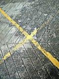 Líneas amarillas cruzadas en el camino Imagenes de archivo