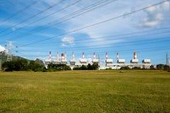 Líneas de alto voltaje y pilones del poder en un agricult plano y verde imagen de archivo