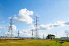Líneas de alto voltaje y pilones del poder en un agricult plano y verde foto de archivo