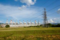 Líneas de alto voltaje y pilones del poder en un agricult plano y verde imagen de archivo libre de regalías