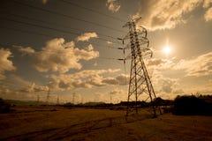 Líneas de alto voltaje y pilones del poder en un agricult plano y verde foto de archivo libre de regalías