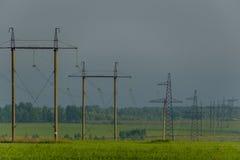 Líneas de alto voltaje y pilones del poder en un paisaje agrícola plano y verde encendido en el amanecer Imagen de archivo libre de regalías