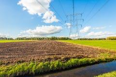 Líneas de alto voltaje y pilones del poder en un paisaje rural imagenes de archivo