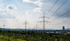 Líneas de alto voltaje y pilones del poder en un paisaje verde, un cielo gris y una chimenea de una central nuclear en el fondo imagenes de archivo