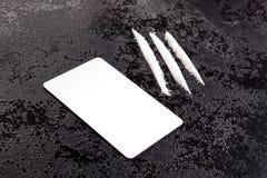 Líneas de la cocaína con la tarjeta en superficie oscura imagenes de archivo
