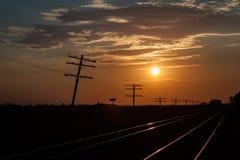 Líneas de telégrafo silueteadas en la salida del sol fotos de archivo libres de regalías
