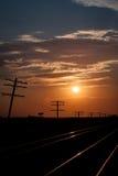 Líneas de telégrafo silueteadas en la salida del sol fotos de archivo
