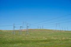 Líneas de transmisión de arriba de la electricidad en una colina, en el verano Imágenes de archivo libres de regalías
