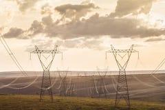 Líneas de transmisión de alto voltaje de los posts de alto voltaje en la puesta del sol Imágenes de archivo libres de regalías