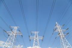 Líneas de transmisión de poder contra el cielo azul Fotografía de archivo