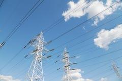 Líneas de transmisión de poder contra el cielo azul Imagenes de archivo