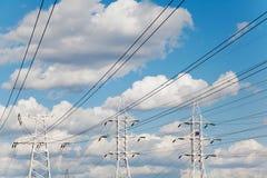 Líneas de transmisión de poder contra el cielo azul Fotos de archivo libres de regalías