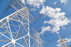 Líneas de transmisión de poder contra el cielo azul Fotos de archivo