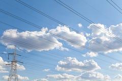 Líneas de transmisión de poder contra el cielo azul Foto de archivo