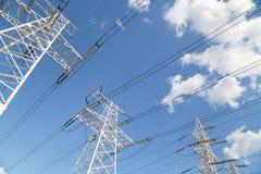 Líneas de transmisión de poder contra el cielo azul Imagen de archivo