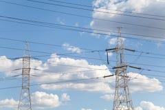 Líneas de transmisión de poder contra el cielo azul Foto de archivo libre de regalías