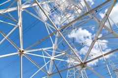 Líneas de transmisión de poder de la visión inferior contra el cielo azul Fotos de archivo libres de regalías