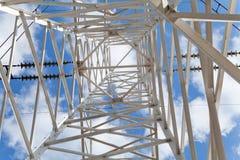Líneas de transmisión de poder de la visión inferior contra el cielo azul Foto de archivo