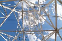 Líneas de transmisión de poder de la visión inferior contra el cielo azul Imagen de archivo