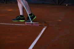Líneas del campo de tenis de la limpieza del hombre Imágenes de archivo libres de regalías