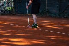 Líneas del campo de tenis de la limpieza del hombre Foto de archivo