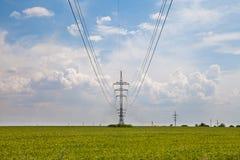 Líneas eléctricas aéreas del pilar en el campo verde Imagen de archivo